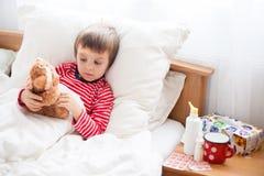 Άρρωστο αγόρι παιδιών που βρίσκεται στο κρεβάτι με έναν πυρετό, στήριξη Στοκ Εικόνες