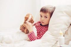 Άρρωστο αγόρι παιδιών που βρίσκεται στο κρεβάτι με έναν πυρετό, στήριξη Στοκ Φωτογραφία