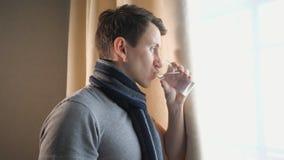 Άρρωστο αρσενικό με την κούπα που βήχει κοντά στο παράθυρο φιλμ μικρού μήκους