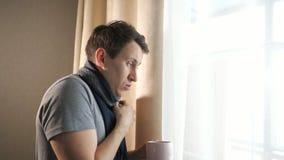 Άρρωστο αρσενικό με την κούπα που βήχει κοντά στο παράθυρο απόθεμα βίντεο