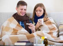 Άρρωστο ζεύγος κάτω από το κάλυμμα που ελέγχει τον πυρετό Στοκ φωτογραφία με δικαίωμα ελεύθερης χρήσης
