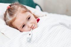 Άρρωστο κορίτσι με ένα θερμόμετρο στο στόμα Γκρινιάρικο πρόσωπο Στοκ φωτογραφία με δικαίωμα ελεύθερης χρήσης