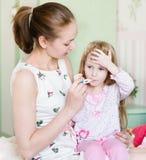 Άρρωστο παιδί με τον υψηλό πυρετό και μητέρα που παίρνει τη θερμοκρασία Στοκ Εικόνες