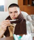 Άρρωστο συνηθισμένο άτομο που κοιτάζει από το θερμόμετρο Στοκ Εικόνες