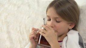 Άρρωστο τσάι λεμονιών κατανάλωσης πορτρέτου παιδιών, λυπημένο ανεπαρκές πρόσωπο κοριτσιών στο κρεβάτι, καναπές απόθεμα βίντεο