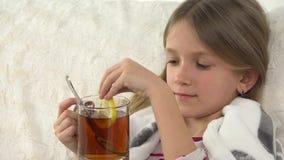 Άρρωστο τσάι λεμονιών κατανάλωσης πορτρέτου παιδιών, λυπημένο ανεπαρκές πρόσωπο κοριτσιών στο κρεβάτι, καναπές 4K φιλμ μικρού μήκους