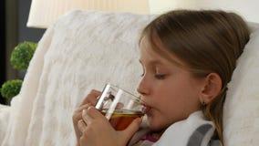 Άρρωστο τσάι λεμονιών κατανάλωσης πορτρέτου παιδιών, λυπημένο ανεπαρκές πρόσωπο κοριτσιών στο κρεβάτι, καναπές 4K απόθεμα βίντεο