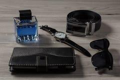 Άρωμα ατόμων, ρολόι, ζώνη δέρματος, σημειωματάριο, γυαλιά ηλίου σε έναν γκρίζο Στοκ εικόνες με δικαίωμα ελεύθερης χρήσης