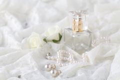 Άρωμα γυναικών ` s στο όμορφο μπουκάλι, ελαφρύ υπόβαθρο με τα acces Στοκ φωτογραφία με δικαίωμα ελεύθερης χρήσης