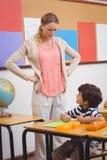 0 δάσκαλος που φαίνεται μαθητής με τα χέρια στα ισχία Στοκ εικόνες με δικαίωμα ελεύθερης χρήσης
