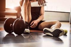 Άσκηση αθλητών και workout στη γυμναστική ικανότητας Το άτομο χαλαρώνουν και το πρωτεϊνικά μπουκάλι και το μήλο κουνημάτων εκμετά στοκ φωτογραφίες