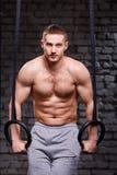 Άσκηση πυρήνων Crossfit Καθορισμένο άτομο που επιλύει στο τράβηγμα UPS γυμναστικής με τα γυμναστικά δαχτυλίδια για τη δύναμη Στοκ Εικόνες