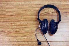 Άσπρα ακουστικά στον ξύλινο πίνακα Στοκ εικόνα με δικαίωμα ελεύθερης χρήσης