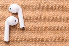 Άσπρα ασύρματα ακουστικά σε μια όμορφη ψάθινη πετσέτα στοκ φωτογραφία με δικαίωμα ελεύθερης χρήσης