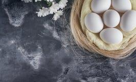 Άσπρα αυγά κοτόπουλου στη φωλιά Πάσχας στο γκρίζο υπόβαθρο Τοπ άποψη, διάστημα αντιγράφων για το κείμενο Στοκ εικόνα με δικαίωμα ελεύθερης χρήσης