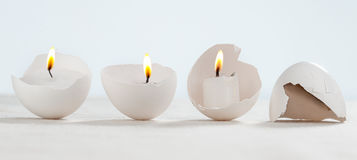 Άσπρα αυγά με τα κεριά φλογών Στοκ Εικόνες
