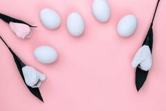 Άσπρα αυγά Πάσχας και τουλίπες λουλουδιών στο ρόδινο υπόβαθρο r στοκ φωτογραφία
