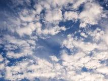 Άσπρα, αυξομειούμενα σύννεφα στο μπλε ουρανό Στοκ Εικόνες