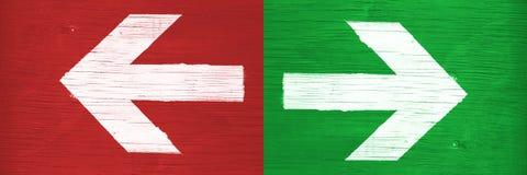 Άσπρα βέλη που δείχνουν τις κατευθύνσεις δεξιά και αριστερά με το χέρι χρωματισμένος στο πράσινο και κόκκινο ξύλινο υπόβαθρο πινα στοκ φωτογραφία με δικαίωμα ελεύθερης χρήσης