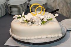 Άσπρα γαμήλια διακοσμημένα κέικ λουλούδια και χρυσά δαχτυλίδια Στοκ φωτογραφία με δικαίωμα ελεύθερης χρήσης