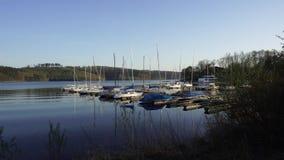 Άσπρα γιοτ βαρκών στο λιμάνι αποβαθρών, λίμνη Sorpesee, Γερμανία απόθεμα βίντεο