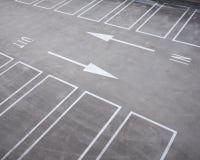 Άσπρα γραμμές και βέλη στο ολλανδικό γκαράζ χώρων στάθμευσης Στοκ Εικόνες