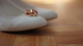 Άσπρα θηλυκά παπούτσια με τα γαμήλια δαχτυλίδια Μετακινηθείτε τον πυροβολισμό απόθεμα βίντεο