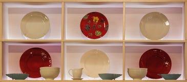 Άσπρα και κόκκινα πιάτα στην προθήκη φιαγμένη από ξύλο με το φωτισμό Στοκ φωτογραφία με δικαίωμα ελεύθερης χρήσης