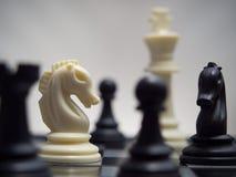 Άσπρα και μαύρα κομμάτια σκακιού σε μια σκακιέρα Στοκ Εικόνες