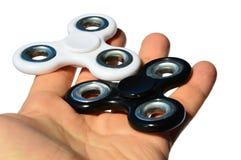 Άσπρα και μαύρα fidget παιχνίδια κλωστών που κρατιούνται στο φοίνικα του ενήλικου αρσενικού προσώπου, άσπρο υπόβαθρο στοκ φωτογραφίες