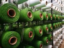 Άσπρα και πράσινα νήματα στα ράφια για τις τεχνητές υφαίνοντας μηχανές χλόης στοκ εικόνες
