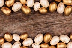 Άσπρα και χρυσά διπλά σύνορα αυγών Πάσχας πέρα από το αγροτικό ξύλο Στοκ Εικόνες