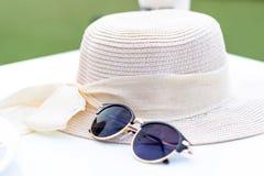 Άσπρα καπέλο αχύρου και γυαλιά ηλίου, εξαρτήματα των γυναικών που προστατεύουν από τον ήλιο όταν ταξίδι στη θάλασσα το καλοκαίρι στοκ φωτογραφίες