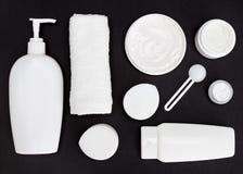 Άσπρα καλλυντικά εμπορευματοκιβώτια στη μαύρη επιφάνεια Στοκ Εικόνες