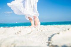 Άσπρα κινούμενα φούστα και πόδια στην άμμο Στοκ φωτογραφία με δικαίωμα ελεύθερης χρήσης