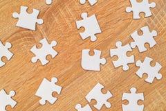 Άσπρα κομμάτια γρίφων τορνευτικών πριονιών που διασκορπίζονται στον ξύλινο πίνακα Στοκ φωτογραφία με δικαίωμα ελεύθερης χρήσης