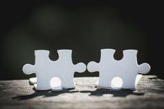2 άσπρα κομμάτια του γρίφου στέκονται στον ξύλινο πίνακα που απομονώνεται στο μαύρο υπόβαθρο, έννοια της σύνδεσης στοκ εικόνα με δικαίωμα ελεύθερης χρήσης