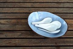Άσπρα κουτάλια στο μπλε πιάτο Στοκ φωτογραφία με δικαίωμα ελεύθερης χρήσης