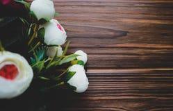 Άσπρα λουλούδια Rununculus σε ένα ξύλινο καφετί υπόβαθρο Στοκ Φωτογραφίες