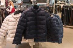 Άσπρα, μαύρα και γκρίζα κάτω παλτά στο ράφι, κατάστημα Στοκ Εικόνες