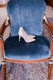 Άσπρα νυφικά παπούτσια στην μπλε καρέκλα Στοκ Φωτογραφίες