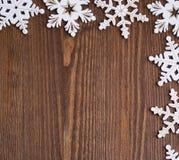 Άσπρα ξύλινα snowflakes σε ένα καφετί ξύλινο υπόβαθρο Στοκ εικόνες με δικαίωμα ελεύθερης χρήσης