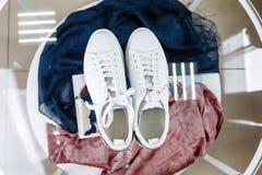 Άσπρα πάνινα παπούτσια με ένα αστέρι φιαγμένο από rhinestones στο τακούνι σε έναν πίνακα γυαλιού στοκ φωτογραφία με δικαίωμα ελεύθερης χρήσης