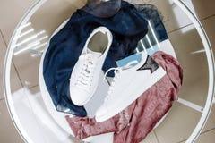 Άσπρα πάνινα παπούτσια με ένα αστέρι φιαγμένο από rhinestones στο τακούνι σε έναν πίνακα γυαλιού στοκ εικόνα