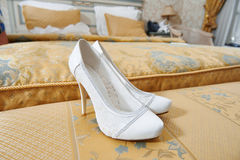 Άσπρα παπούτσια της νύφης στην κρεβατοκάμαρα Στοκ Εικόνες
