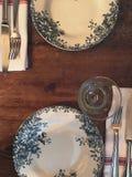 Άσπρα πιάτα που διακοσμούνται με τα λουλούδια και τις εγκαταστάσεις στο μπλε χρώμα στοκ φωτογραφία με δικαίωμα ελεύθερης χρήσης