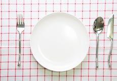 άσπρα πιάτο μαχαιριών και κουτάλι δικράνων στο κόκκινο που ελέγχεται Στοκ φωτογραφίες με δικαίωμα ελεύθερης χρήσης