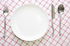 άσπρα πιάτο μαχαιριών και κουτάλι δικράνων στο κόκκινο που ελέγχεται Στοκ φωτογραφία με δικαίωμα ελεύθερης χρήσης
