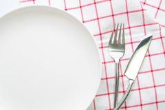 άσπρα πιάτο μαχαιριών και κουτάλι δικράνων στο κόκκινο που ελέγχεται Στοκ εικόνες με δικαίωμα ελεύθερης χρήσης