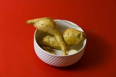 Άσπρα πρωτεϊνικά τρόφιμα φετών κομματιών γλυκών πατατών στο απομονωμένο κόκκινο υπόβαθρο στοκ φωτογραφία με δικαίωμα ελεύθερης χρήσης